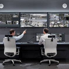 control room; operator; monitors; monitor wall; bosch vido management system; user interface; two persons; men, pointing to monitor; security room; security control room